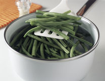 Putting the green beans in the boiling water Royalty Free Stock Photography
