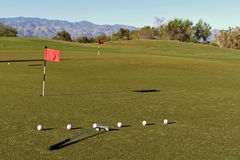 At the putting green. Clubs and balls at the putting green at the sunset and mountains on the background Royalty Free Stock Images