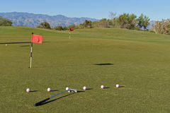 At the putting green. Clubs and balls at the putting green at the sunset and mountains on the background Royalty Free Stock Photo
