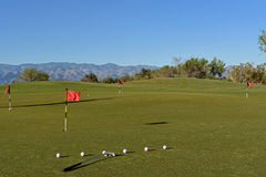At the putting green. Clubs and balls at the putting green at the sunset and mountains on the background Royalty Free Stock Photography