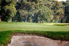 Putting green con el rastrillo en arc?n de la arena en el campo de golf foto de archivo libre de regalías
