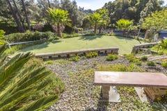 Putting green en el hogar de Fallbrook con un banco y las palmeras Foto de archivo