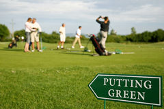 Putting green. Putting green guidance board in the foreground and golf players out of focus on the background Royalty Free Stock Image