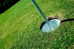 Putting green hole. A golf hole on a green of a golfcourse with focus on the flag royalty free stock photography
