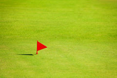 Putting green with red flag marker on golf course Royalty Free Stock Photo