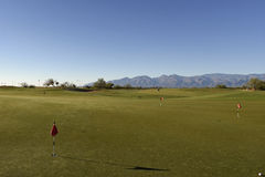 At the putting green. Putting green at the sunset and mountains on the background Royalty Free Stock Images