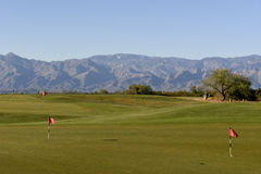 At the putting green. Putting green at the sunset and mountains on the background Royalty Free Stock Photo