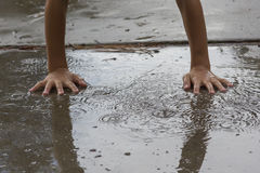 Putting hands in a puddle. Stock Images
