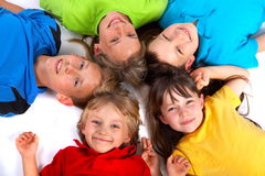 Putting heads together. A group of children lie down with their heads touching, in a circular formation stock images