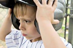 Putting on Helment. Little boy putting on his batting helmet Stock Photos