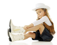 Putting on Her Cowgirl Boots. A young cowgirl putting on her boots.  On a white background Royalty Free Stock Photo
