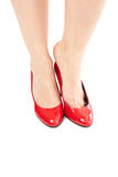 Putting on her shoes. Woman legs standing and putting on her red shoes Stock Photos