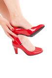 Putting on her shoes. Woman putting on her sexy red shoes with high heels Stock Photo