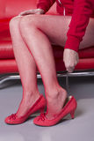 Putting on high heel shoe using a shoehorn Royalty Free Stock Photos