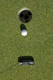 Putting into the hole. Golfer putting the ball into the hole for a low score Stock Image
