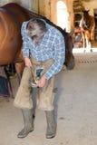 Putting hoof on horse Royalty Free Stock Photos