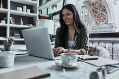 Putting ideas into something real. Attractive young smiling woman using laptop while sitting in restaurant stock image