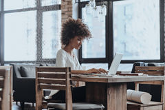 Putting ideas into something real. Beautiful young African woman in smart casual wear working using computer while sitting in cafe stock image