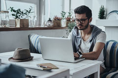 Putting ideas into something real. Handsome young modern man in eyewear using computer while sitting on the sofa royalty free stock image