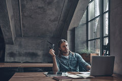 Putting ideas into something real. Thoughtful young man holding eyeglasses and working using computer while sitting at the office desk near the window royalty free stock photos