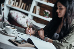 Putting ideas into something real. Thoughtful young woman writing something down in her notebook while sitting at her working place stock photos
