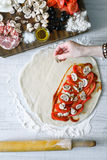 Putting ingredients  for calzone on the dough top view Royalty Free Stock Images