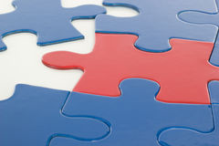 Putting jigsaw puzzle in teamwork together Royalty Free Stock Image