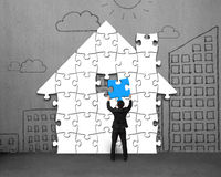 Putting last blue puzzles in house shape on wall. Putting last blue puzzles in house shape on concrete wall Royalty Free Stock Photos