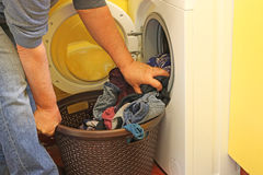 putting laundry int a washing machine. Royalty Free Stock Photography