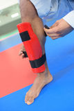 Putting on leg guard Stock Images