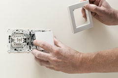 Putting light switch cover Stock Photos