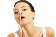 Putting on lip gloss Stock Photo