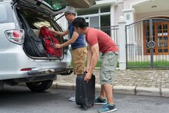 Putting luggage in car. Friends travelers putting backpack in the trunk Royalty Free Stock Photography