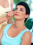 Putting make up. Stylist putting some make up on mature attractive woman Stock Photo