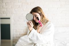 Putting on makeup in the morning. Young Hispanic woman in a bathrobe getting ready and putting some makeup on in the morning Stock Images
