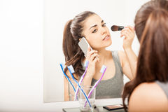 Putting on makeup and talking on the phone. Busy young woman taking a call on her smartphone while getting ready for work and putting some makeup on Stock Image