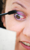 Putting mascara on eyelashes Stock Photo