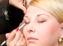 Putting on models eye make up Stock Photography
