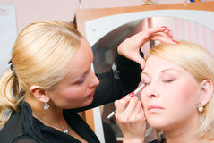 Putting on models eye make up Royalty Free Stock Photos
