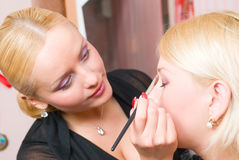 Putting on models eye make up Royalty Free Stock Images