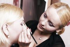 Putting on models eye make up Stock Photo