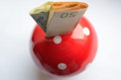 Putting money euro into a piggy bank mushroom Royalty Free Stock Photography