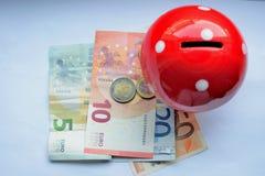 Putting money euro into a piggy bank mushroom Stock Images