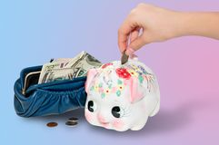 Putting money into the piggy bank Royalty Free Stock Images
