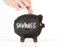 Putting money on a piggy bank Stock Photos
