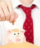 Putting money on a piggy bank Stock Image