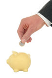 Putting money in a piggy bank Royalty Free Stock Photos
