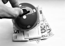 Putting money into a piggy bank mushroom black and white Stock Photography