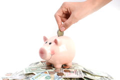 Putting money in a pink piggy bank standing on a pile of coins and bills, suggesting money savings concept Stock Photo