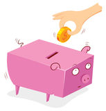 Putting money in to a pig bank Royalty Free Stock Image